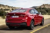 Driving 2017 BMW X4 in Melbourne Red Metallic from a rear right view