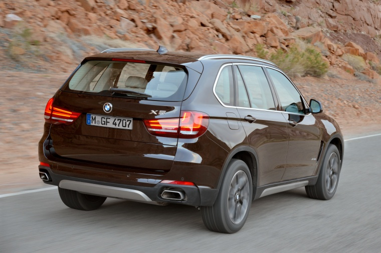 Driving 2014 BMW X5 xDrive50i in Sparkling Brown Metallic from a rear right view