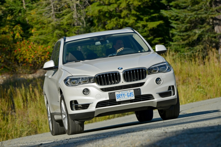 Driving 2017 BMW X5 xDrive50i in Alpine White from a front right view