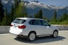 Driving 2017 BMW X5 xDrive50i in Alpine White from a rear right three-quarter view