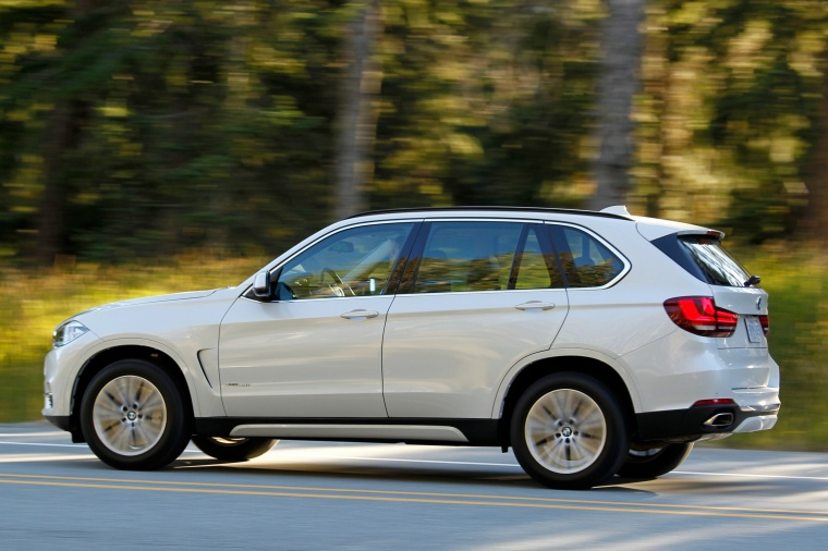 Driving 2018 BMW X5 xDrive50i in Alpine White from a rear left three-quarter view