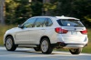 Driving 2018 BMW X5 xDrive50i in Alpine White from a rear left view