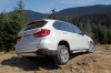 Driving 2018 BMW X5 xDrive50i in Alpine White from a rear right three-quarter view