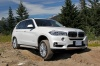 Driving 2018 BMW X5 xDrive50i in Alpine White from a front right three-quarter view