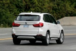 Picture of a driving 2018 BMW X5 xDrive50i in Alpine White from a rear right perspective