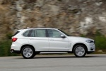 Picture of a driving 2018 BMW X5 xDrive50i in Alpine White from a right side perspective