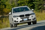 Picture of a driving 2018 BMW X5 xDrive50i in Alpine White from a front right perspective