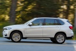 Picture of a driving 2018 BMW X5 xDrive50i in Alpine White from a left side perspective