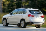 Picture of a driving 2018 BMW X5 xDrive50i in Alpine White from a rear left perspective