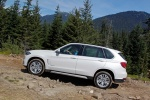 Picture of a driving 2018 BMW X5 xDrive50i in Alpine White from a side perspective