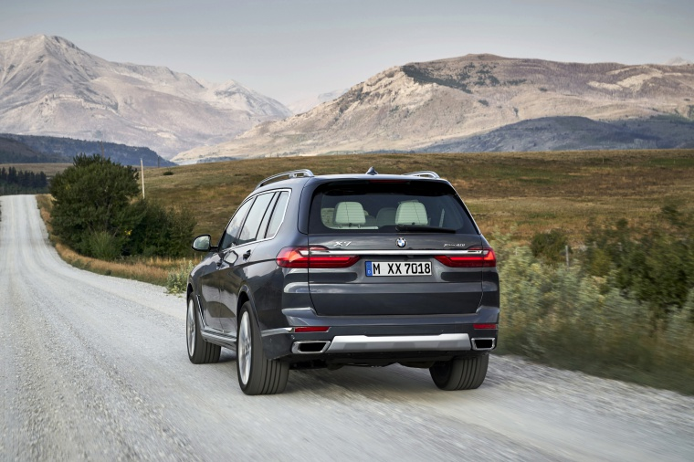 Driving 2019 BMW X7 xDrive40i AWD in Arctic Gray Metallic from a rear view