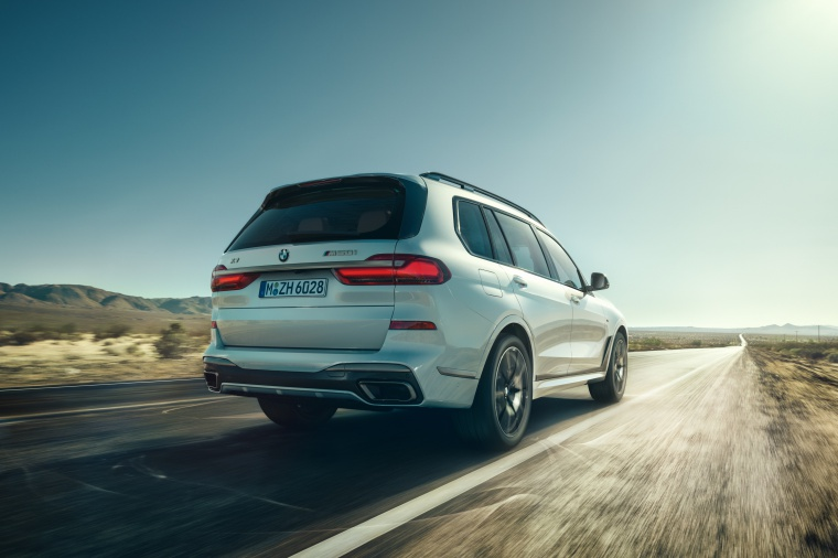Driving 2019 BMW X7 M50i AWD in Alpine White from a rear right three-quarter view