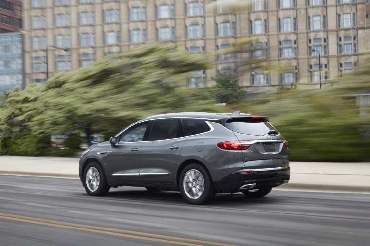 Driving 2019 Buick Enclave in Satin Steel Metallic from a rear left three-quarter view