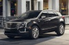 Driving 2017 Cadillac XT5 AWD in Dark Granite Metallic from a front left three-quarter view