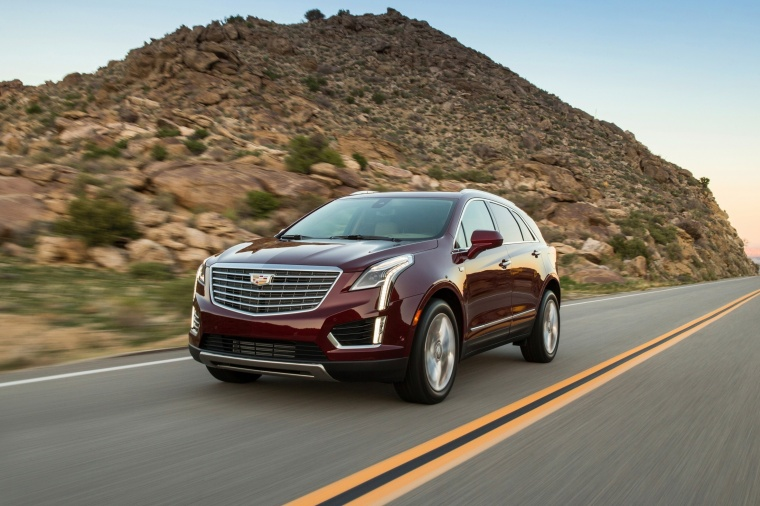 Driving 2018 Cadillac XT5 AWD in Red Passion Tintcoat from a front left three-quarter view