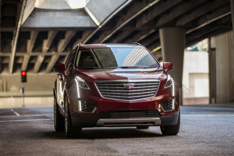 Driving 2018 Cadillac XT5 AWD in Red Passion Tintcoat from a front right view