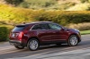 Driving 2018 Cadillac XT5 AWD in Red Passion Tintcoat from a rear right three-quarter view