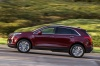 Driving 2018 Cadillac XT5 AWD in Red Passion Tintcoat from a side view