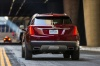 Driving 2018 Cadillac XT5 AWD in Red Passion Tintcoat from a rear view
