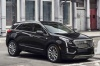 Driving 2018 Cadillac XT5 AWD in Dark Granite Metallic from a front right three-quarter view