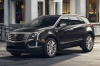 Driving 2018 Cadillac XT5 AWD in Dark Granite Metallic from a front left three-quarter view