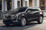Picture of a driving 2019 Cadillac XT5 AWD in Dark Granite Metallic from a front left three-quarter perspective