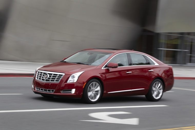 Driving 2016 Cadillac XTS AWD in Crystal Red Tintcoat from a front left three-quarter view