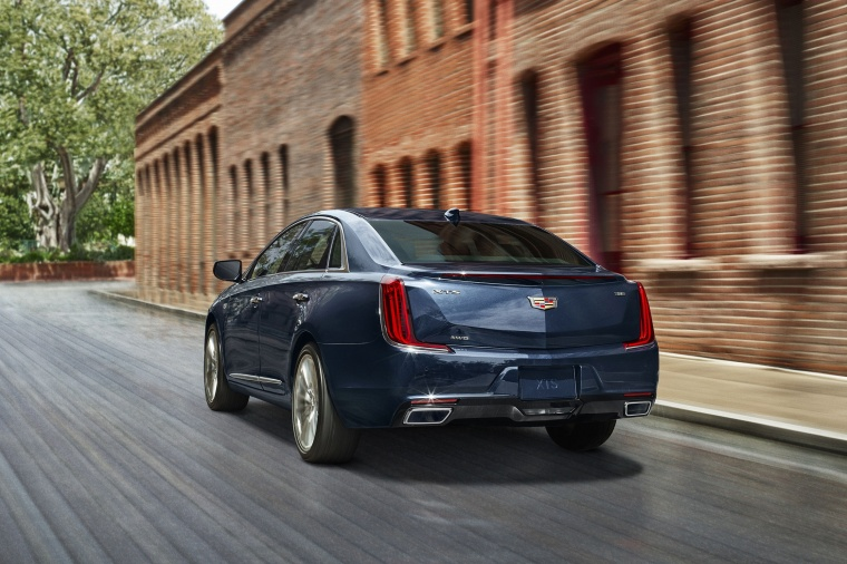 Driving 2018 Cadillac XTS in Dark Adriatic Blue Metallic from a rear left view