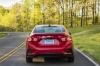 Driving 2018 Chevrolet Cruze Premier RS Sedan in Red Hot from a rear view