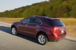 Picture of a driving 2014 Chevrolet Equinox LTZ in Crystal Red Tintcoat from a rear left three-quarter perspective