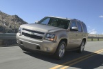 Picture of a driving 2014 Chevrolet Tahoe LTZ in Champagne Silver Metallic from a front left three-quarter perspective
