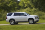 Picture of a driving 2016 Chevrolet Tahoe in Silver Ice Metallic from a side perspective