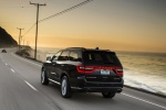 Picture of a driving 2014 Dodge Durango Citadel in Brilliant Black Crystal Pearlcoat from a rear left three-quarter perspective