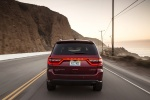 Picture of a driving 2014 Dodge Durango Limited AWD in Deep Cherry Red Crystal Pearlcoat from a rear perspective