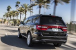 Picture of a driving 2016 Dodge Durango Citadel in Brilliant Black Crystal Pearlcoat from a rear left perspective