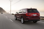 Picture of a driving 2016 Dodge Durango Limited AWD in Deep Cherry Red Crystal Pearlcoat from a rear left three-quarter perspective