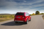 Picture of a driving 2019 Dodge Journey Crossroad AWD in Redline 2 Coat Pearl from a rear right perspective