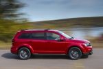Picture of a driving 2019 Dodge Journey Crossroad AWD in Redline 2 Coat Pearl from a side perspective