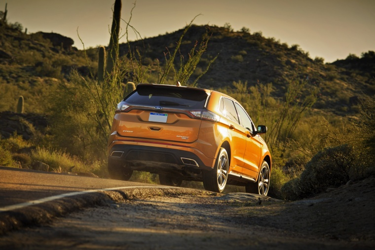 Driving  Ford Edge Sport In Electric Spice Metallic From A Rear Right View