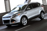 Picture of a driving 2014 Ford Escape Titanium 4WD in Ingot Silver Metallic from a front left three-quarter perspective