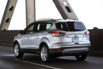 Picture of a driving 2014 Ford Escape Titanium 4WD in Ingot Silver Metallic from a rear left three-quarter perspective