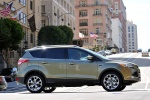 Picture of a driving 2014 Ford Escape Titanium 4WD in Ginger Ale Metallic from a right side perspective