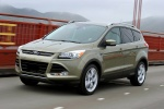 Picture of a driving 2014 Ford Escape Titanium 4WD in Ginger Ale Metallic from a front left three-quarter perspective
