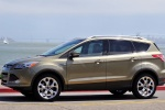 Picture of a driving 2014 Ford Escape Titanium 4WD in Ginger Ale Metallic from a left side perspective