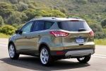 Picture of a driving 2014 Ford Escape Titanium 4WD in Ginger Ale Metallic from a rear left three-quarter perspective