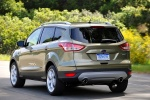 Picture of a driving 2014 Ford Escape Titanium 4WD in Ginger Ale Metallic from a rear left perspective