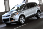 Picture of a driving 2015 Ford Escape Titanium 4WD in Ingot Silver Metallic from a front left three-quarter perspective