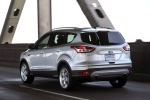 Picture of a driving 2015 Ford Escape Titanium 4WD in Ingot Silver Metallic from a rear left three-quarter perspective