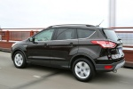 Picture of a driving 2015 Ford Escape in Tuxedo Black from a rear left three-quarter perspective