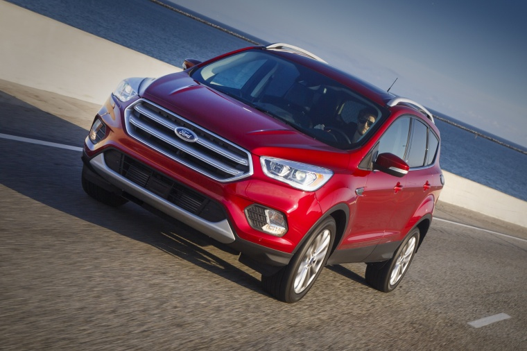 Driving 2017 Ford Escape Titanium in Ruby Red Metallic Tinted Clearcoat from a front left view